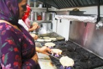 Woman roasting roti- Indian bread