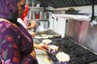 Woman roasting roti- Indian bread