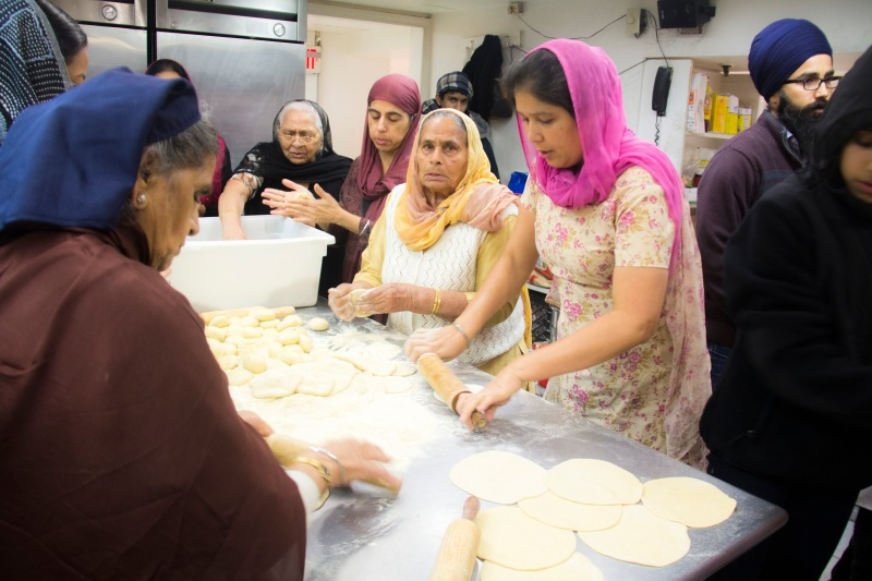 Woman rolling and kneading roti- Indian bread