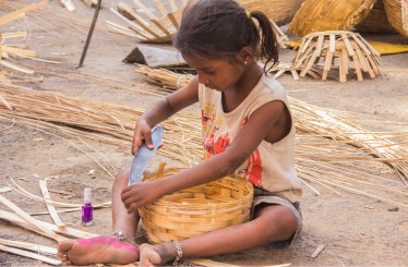 Little girl weaving a basket